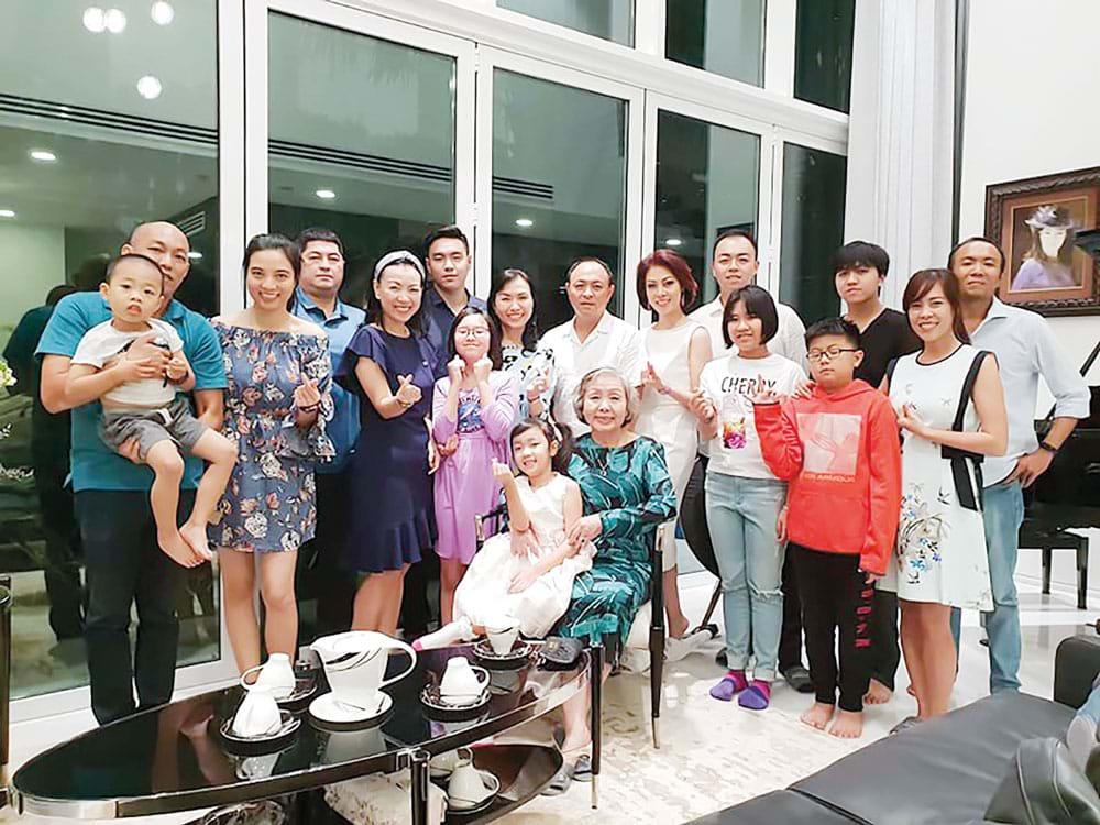 Bà Nguyễn Thị Sơn người mặt áo xanh ngồi ghế trong buổi chụp ảnh chung cùng đại gia đinh